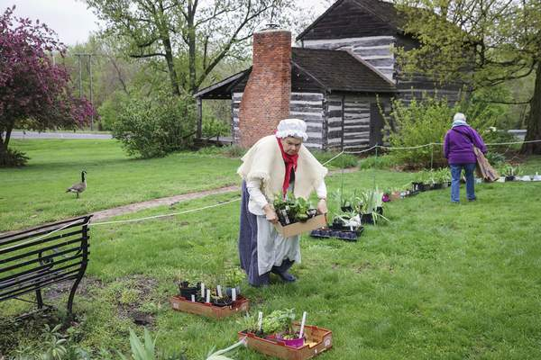 Mike Moore | The Journal Gazette  Settler Pam Oleson helps customers on Friday by boxing their herb purchases during the Annual Herb and Perennial Plant Sale at the Historic Swinney Homestead.