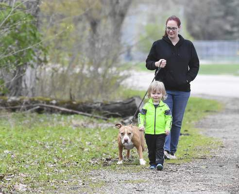 Michelle Davies | The Journal Gazette  Maximus Isenhour, 2, enjoys a walk with his mother Jessica Bjorklund and Sasha, a 10-year-old pitbull, Monday morning at Foster Park.