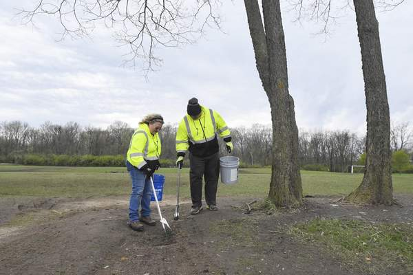 Michelle Davies | The Journal Gazette  Fort Wayne Parks and Recreation Department workers Charla Hilton, left, and Ryan Dellinger work on cleaning up garbage left at Tillman Park after a soccer festival over the weekend. Park cleanup usually requires 1 to 3 people, however, 16 workers were called in Monday morning to clean up the debris.