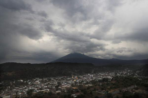This Thursday, May 2, 2019 photo shows a view of the Mexican village Santiago Xalitzintla as the looming Popocatepetl volcano spews ash. Santiago Xalitzintla has the distinction of being the community closest to Popocatepetl, a crater that has increasingly been belching lava and spewing ash as far as Mexico City, 56 miles to the northwest. (AP Photo/Marco Ugarte)