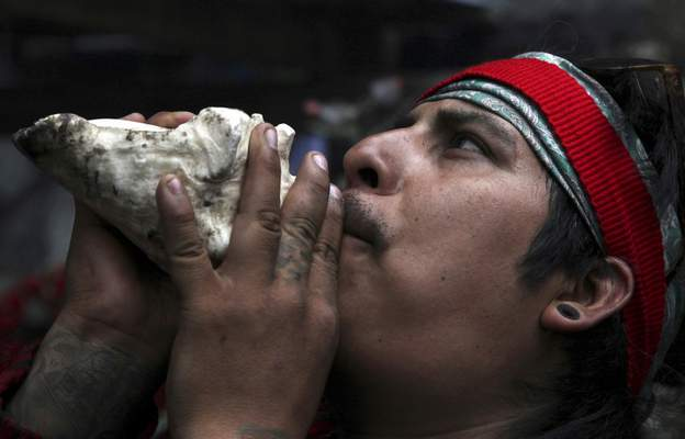 In this Friday, May 3, 2019 photo, a resident blows on a conch shell to honor Tonantzin, the Aztec mother earth goddess that's often celebrated alongside the Virgin Mary, during the Day of the Cross celebrations on the flanks of the Iztaccíhuatl volcanoor The Sleeping Woman (the volcano resembles a reclining female), near Santiago Xalitzintla, Mexico. (AP Photo/Marco Ugarte)
