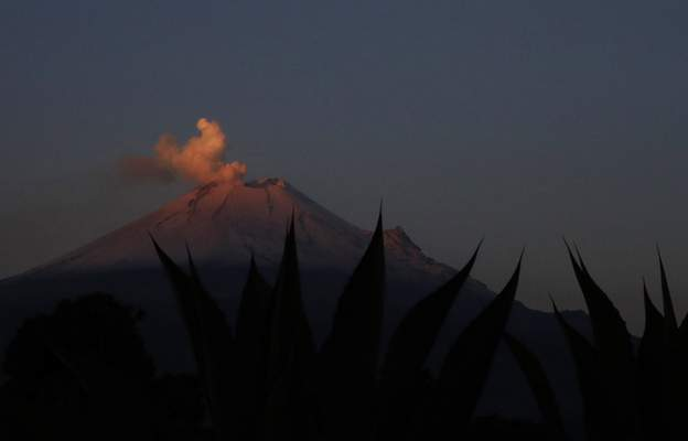 In this Thursday, May 2, 2019 photo, the Popocatepetl volcano releases a plume of ash as seen from the flanks of the Iztaccíhuatl volcano, near Santiago Xalitzintla, Mexico. Veronica Agustin says the community has gotten used to living with Don Goyo, a nickname for Popocatepetl. (AP Photo/Marco Ugarte)