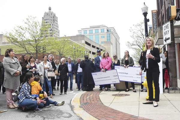 Shindigz celebrated the grand opening of its new corporate headquarters in downtown Fort Wayne Friday morning with Wendy Moyle, co-owner, helping to present checks to five organizations to demonstrate their commitment to their new location. (Photos by Michelle Davies | The Journal Gazette)