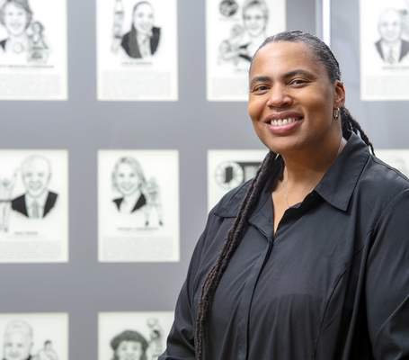Photos by Doug McSchooler | For The Journal-Gazette Leslie Johnson poses by the wall of portraits showing new members to the Indiana High School Basketball Hall of Fame in New Castle. Johnson is the seventh leading scorer in IHSAA girls basketball history.