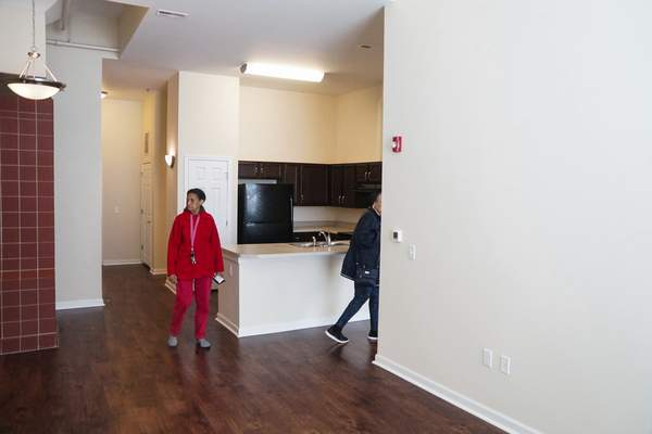 Mike Moore | The Journal Gazette  Guests explore the interior of a single bedroom apartment at Bottle Works Lofts on East Pontiac Street on Monday after the grand opening hosted by the city of Fort Wayne, Miller Valentine officials, Vincent Village and community leaders.