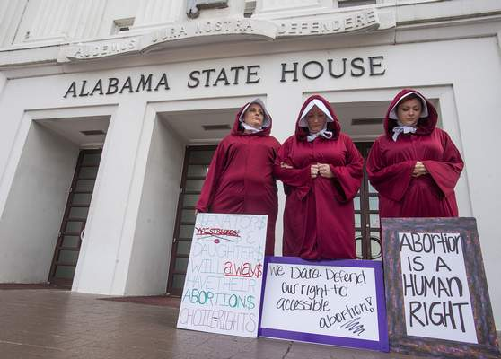 CORRECTS LAST NAME TO HARTLINE INSTEAD OF HARDLINE - Bianca Cameron-Schwiesow, from left, Kari Crowe and Margeaux Hartline, dressed as handmaids, take part in a protest against HB314, the abortion ban bill, at the Alabama State House in Montgomery, Ala., on Wednesday April 17, 2019. (Mickey Welsh/The Montgomery Advertiser via AP)
