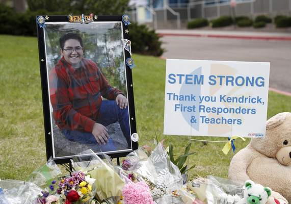 A photograph of student Kendrick Castillo stands amid a display of tributes outside the STEM School Highlands Ranch a week after the attack on the school that left Castillo dead and others injured, Tuesday, May 14, 2019, in Highlands Ranch, Colo. (AP Photo/David Zalubowski)