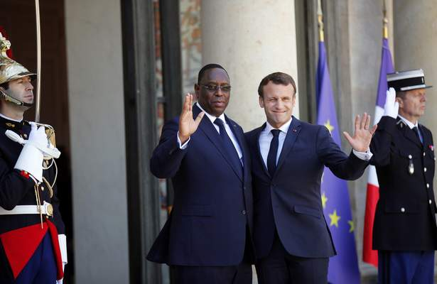 Senegal's President Macky Sall, center left, is greeted by French President Emmanuel Macron as he arrives at the Elysee Palace, in Paris, Wednesday, May 15, 2019. Several world leaders and tech bosses are meeting in Paris to find ways to stop acts of violent extremism from being shown online. (AP Photo/Francois Mori)