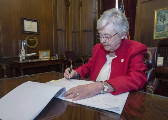 Associated Press Alabama Gov. Kay Ivey signs a bill Wednesday in Montgomery that virtually outlaws abortion in the state. Supporters hope it leads to the end of Roe v. Wade.