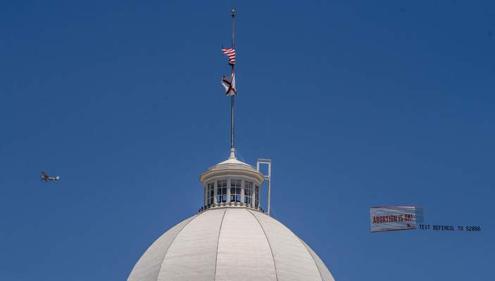 """Associated Press A banner reading """"Abortion is OK"""" flies over the Capitol in Montgomery, Ala., on Wednesday. People on both sides of the abortion issue are ready for a fight after the state's abortion ban passed."""