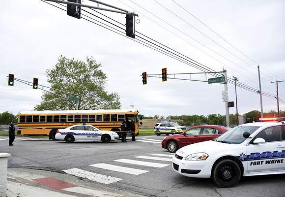 Police gather at  Vance Avenue and Reed Road on Tuesday afternoon to investigate after a crossing guard was struck by a school bus outside Lane Middle School. (Katie Fyfe   The Journal Gazette)
