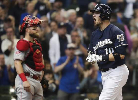 Milwaukee Brewers' Yasmani Grandal celebrates his two-run home run in front of Cincinnati Reds catcher Tucker Barnhart during the sixth inning of a baseball game Wednesday, May 22, 2019, in Milwaukee. (AP Photo/Morry Gash)