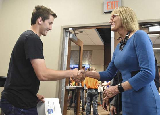 Lt. Gov. Suzanne Crouch congratulates Northrop student Brian Pruse after he signed a letter of intent Wednesday to work with Trademarc Remodeling & Construction LLC.