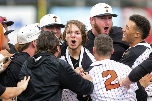 Pete Caster | For The Journal Gazette  Indiana Tech players mob Jake DeFries, center, after his 10th-inning walk-off single propelled the Warriors past Bellevue in Game 1 of the NAIA World Series on Friday at Harris Field in Lewiston, Idaho.