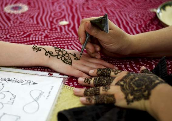 A visitor to Arab Fest has henna applied Saturday at Headwaters Park.