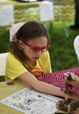Katie Fyfe | The Journal Gazette Myla Kempf, 8, gets a henna design on her hand during Arab Festival at Headwaters Park in Fort Wayne on Saturday, June 1st, 2019.