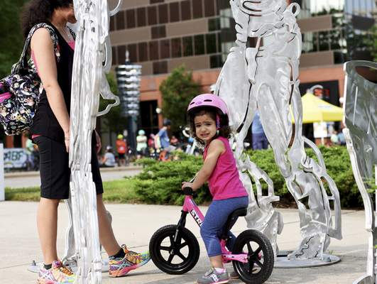 Mikaela Villa, 2, rides her bike near the Arts United Center  with her mom, Luisa.