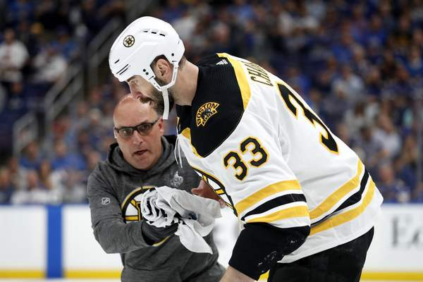 Associated Press Bruins defenseman Zdeno Chara is helped off the ice Monday after getting hit in the face with the puck during Game 4.