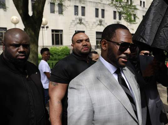 Musician R. Kelly, right, departs the Leighton Criminal Court building after pleading not guilty to 11 additional sex-related charges, Thursday, June 6, 2019, in Chicago. (AP Photo/Amr Alfiky)