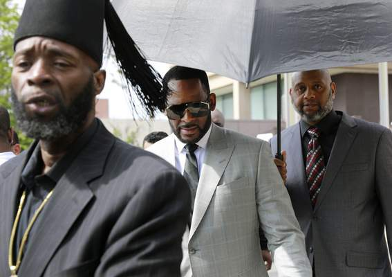 Musician R. Kelly, center, departs the Leighton Criminal Court building after pleading not guilty to 11 additional sex-related charges, Thursday, June 6, 2019, in Chicago. (AP Photo/Amr Alfiky)