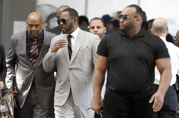 Musician R. Kelly, center, arrives at the Leighton Criminal Court building for an arraignment on new sex-related felonies Thursday, June 6, 2019, in Chicago. Thursday's hearing comes a week after prosecutors announced the new counts, including four of aggravated criminal sexual assault. (AP Photo/Charles Rex Arbogast)