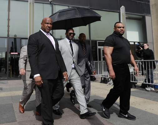 Musician R. Kelly, center, departs from the Leighton Criminal Court building after pleading not guilty to 11 additional sex-related charges, Thursday, June 6, 2019, in Chicago. (AP Photo/Amr Alfiky)