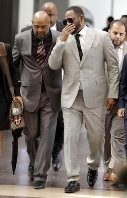 Musician R. Kelly, right, arrives at the Leighton Criminal Court building for an arraignment on 11 new sex-related felonies Thursday, June 6, 2019, in Chicago. Thursday's hearing comes a week after prosecutors announced the new counts, including four of aggravated criminal sexual assault. (AP Photo/Charles Rex Arbogast)