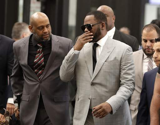 Musician R. Kelly, right, arrives at the Leighton Criminal Court building for an arraignment on new sex-related felonies Thursday, June 6, 2019, in Chicago. Thursday's hearing comes a week after prosecutors announced the new counts, including four of aggravated criminal sexual assault. (AP Photo/Charles Rex Arbogast)
