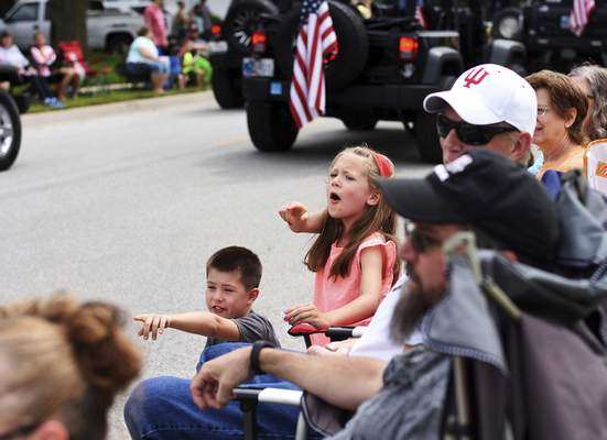 Katie Fyfe | The Journal Gazette  Mallory Sajecki, 6, and Gavin Sajecki, 9, wave at the floats going by during the Canal Days Parade in New Haven on Saturday.