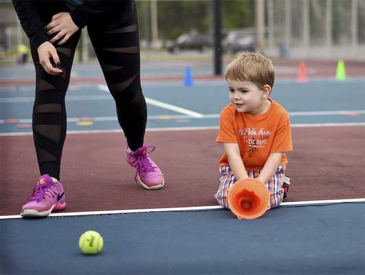Katie Fyfe | The Journal Gazette  Sam Zur Brugg, 3, practices catching the ball during PeeWee Tennis class at Jury Park in New Haven on Tuesday.