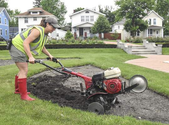 Michelle Davies | The Journal Gazette Nicole Roth, gardener with Fort Wayne Parks Department, tills a flower bed in preparation for planting annuals Tuesday morning at Lakeside Park.