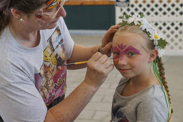 Mike Moore | The Journal Gazette  Jayda Wilson, 6, gets a colorful mask painted on her face during Germanfest at Headwaters Park on Friday.