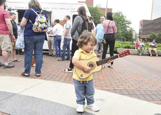 Michelle Davies | The Journal Gazette  Hake Tarango, 2, of Fort Wayne, works on his chords while attending Thursday's opening of Lunch on the Square. Lunch on the Square takes place11:30 a.m. to 1 p.m. Thursdays in June, July and August at Freimann Square.