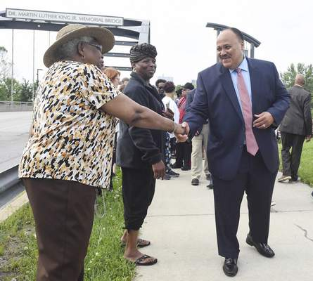 Michelle Davies | The Journal Gazette  Martin Luther King III greets Anne Spann, left, and Shirley Hall, center, both of Fort Wayne, after placing a wreath at the bridge named for his father, the Rev. Martin Luther King Jr. Martin Luther King III spoke in downtown Fort Wayne late Wednesday night.