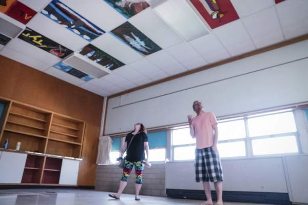 Mike Moore | The Journal Gazette  Kimberly Harber, left, and Chris Strong look for ceiling tiles painted by their classmates on Saturday while visiting the New Haven Middle School.