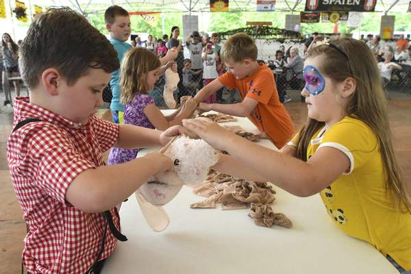 Michelle Davies | The Journal Gazette  Jaeger Heidenreich, 7, and Laela Combs, 7, right, both of Fort Wayne, work together to compete in Ferkelwurst Stuffin', a piglet sausage stuffing game, Friday afternoon at Germanfest. The pair competed toget three stuffed pigs into pantyhose faster than their competitors. They came in third place. Germanfest runs through Sunday.