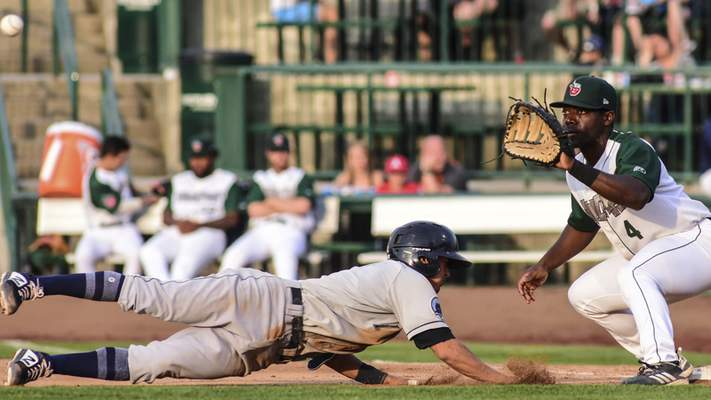 Mike Moore | The Journal Gazette TinCaps first baseman Lee Solomon prepares to catch the ball as a Lake County player dives for the bag in the fourth inning at Parkview Field on Tuesday.