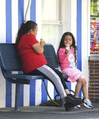 Michelle Davies | The Journal Gazette  Jazlyn Vazquez, 5, enjoys an ice cream cone with her grandmother Maria Gaytan, both of Fort Wayne, Friday morning at Zesto's on Broadway.