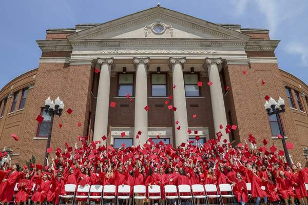 Mike Moore | The Journal Gazette  Following a centuries-old tradition, graduating seniors of North Side High School throw their caps into the air on the steps outside the school on Monday.
