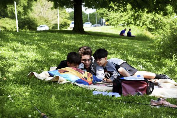 Katie Fyfe | The Journal Gazette  The Vasquez brothers enjoy a nice spot to relax while the rest of their family fishes at Lakeside Park on Sunday.