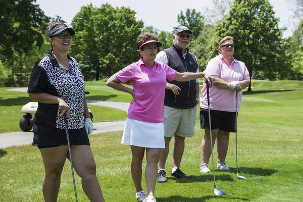 Mike Moore | The Journal Gazette  Parkview Physicians Group golf team members, from left, Carrie Hoffman, Kara Warrener, Jim Chapman and Katie McAllister watch teammate Janet Prendergast, not shown, tee off on the 18th hole of the Vera Bradley Classic golf tournament on Monday to raise donations for breast cancer research at the Sycamore Hills Golf Club.