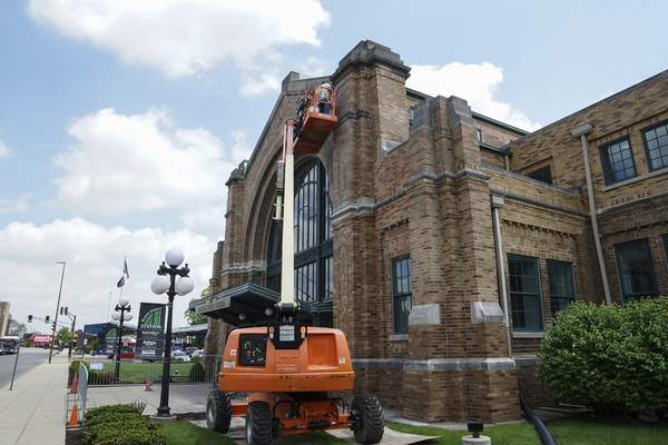 Mike Moore | The Journal Gazette Restoration crews work high above Baker Street on Wednesday to replace bricks to the front of the historic Baker Street Station downtown.