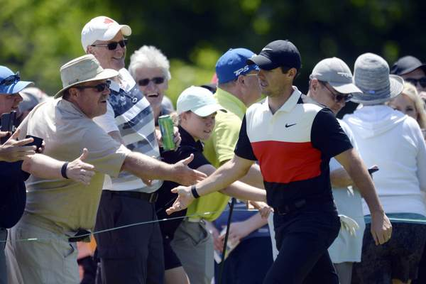 Associated Press Fans reach out to shake hands with Rory McIlroy as he walks to the third tee during the third round of the Canadian Open in Ancaster, Ontario, on Saturday.