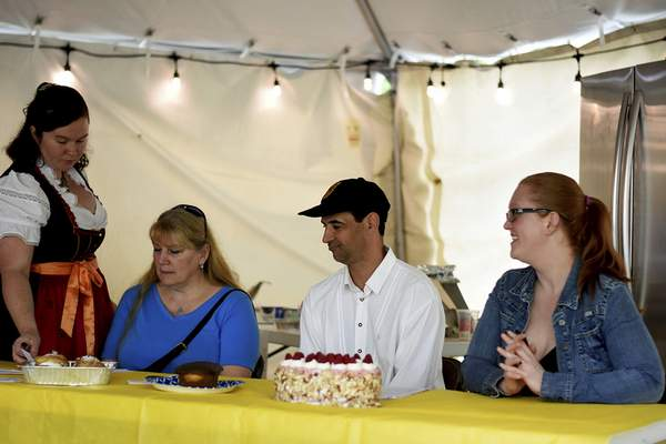 Katie Fyfe | The Journal Gazette  Judges Lisa Wolf, Chef Cornell Taubert, and Lindsay Miller prepare to taste the different German baked goods during the 18th annual Germanfest Bake Off at Headwaters Park on Sunday.