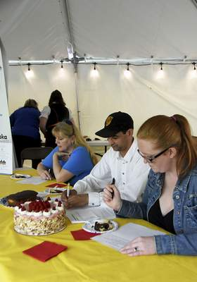 Katie Fyfe | The Journal Gazette  Judges Lisa Wolf, Chef Cornell Taubert, and Lindsay Miller write their comments during the 18th annual Germanfest Bake Off at Headwaters Park on Sunday.