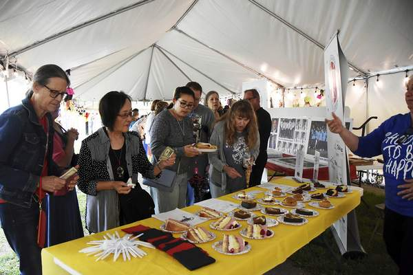 Katie Fyfe | The Journal Gazette  Festival-goers line up to buy baked goods once the competition wraps up during the 18th annual Germanfest Bake Off at Headwaters Park on Sunday.