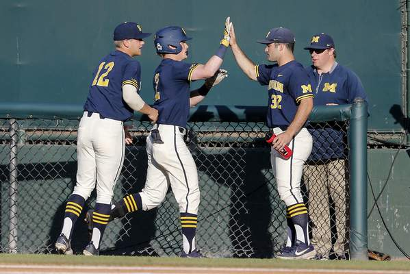 Michigan's Jack Blomgren, second from left, is greeted by teammates after hitting a a single during the second inning of an NCAA college baseball tournament super regional game in Los Angeles, Sunday, June 9, 2019. (AP Photo/Ringo H.W. Chiu)
