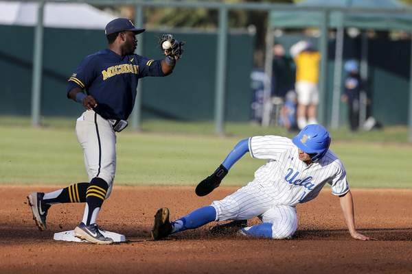 UCLA's Mikey Perez, right, slides safely into second base against Michigan's Ako Thomas during the second inning of an NCAA college baseball tournament super regional game in Los Angeles, Sunday, June 9, 2019. (AP Photo/Ringo H.W. Chiu)