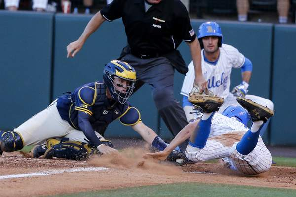 Michigan catcher Joe Donovan, front left, tags out UCLA's Jeremy Ydens, front right, during the fourth inning of an NCAA college baseball tournament super regional game in Los Angeles, Sunday, June 9, 2019. (AP Photo/Ringo H.W. Chiu)
