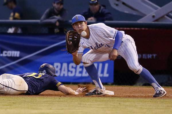 Michigan's Jimmy Kerr, left, dives into first base under the tag attempt by UCLA's Michael Toglia during the fifth inning of an NCAA college baseball tournament super regional game in Los Angeles, Sunday, June 9, 2019. (AP Photo/Ringo H.W. Chiu)